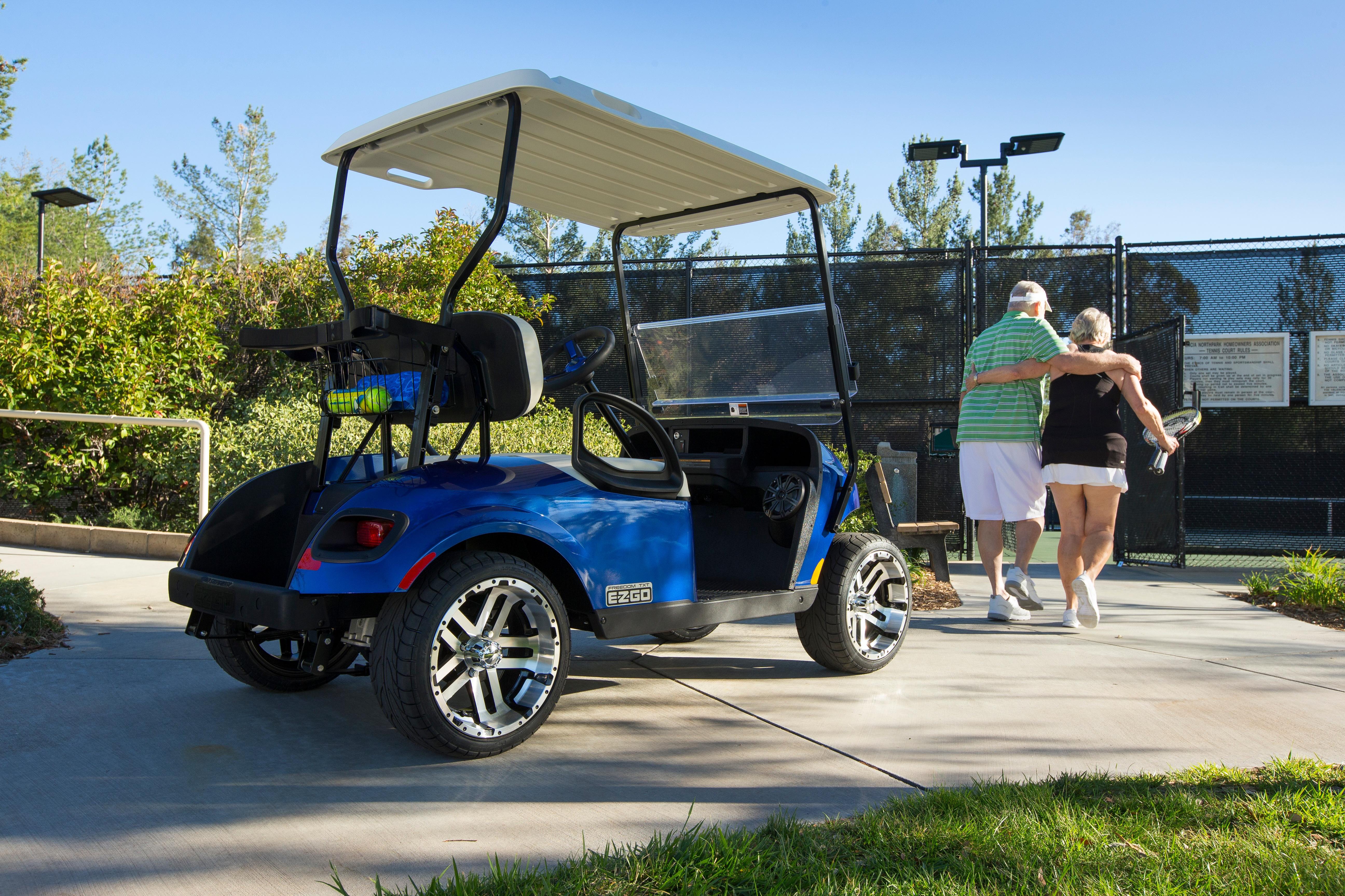 EZGO_Freedom TXT_Lifestyle Image_Tennis Couple Walking Away from Vehicle_Blue.jpg
